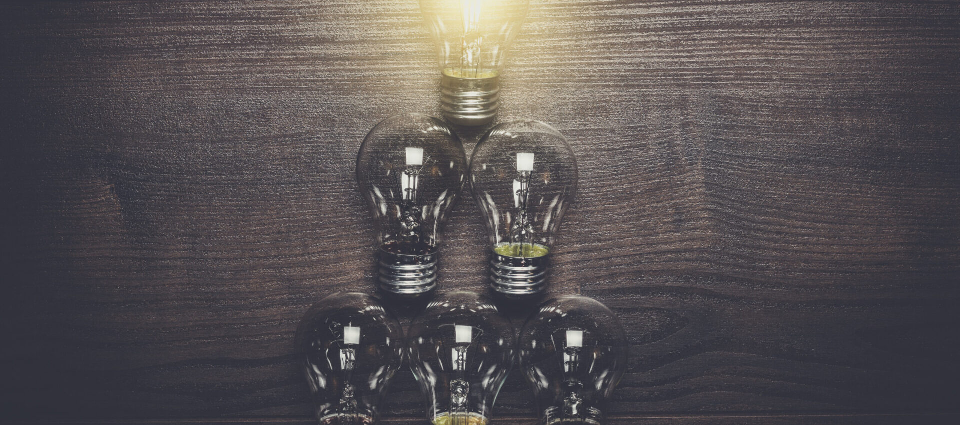 glowing bulb leadership concept on brown wooden background